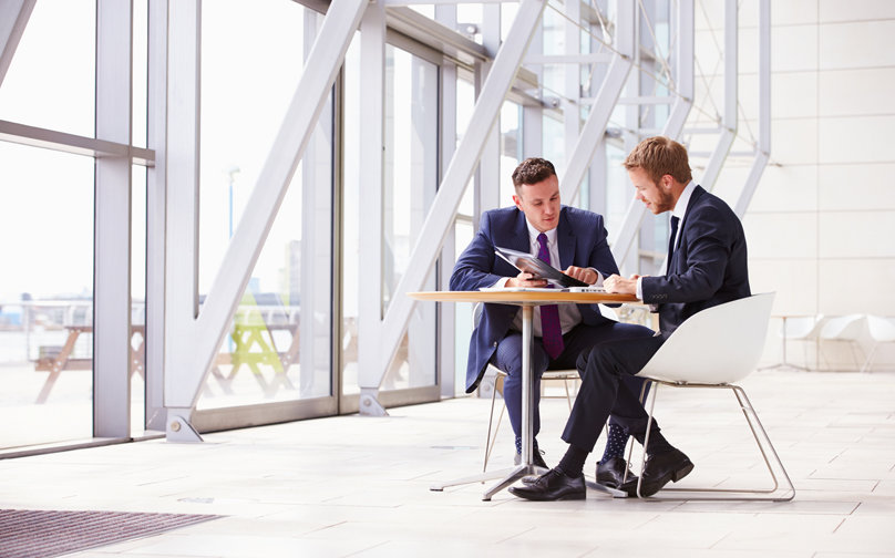 stock-photo-73550601-two-business-colleagues-at-meeting-in-modern-office-interior